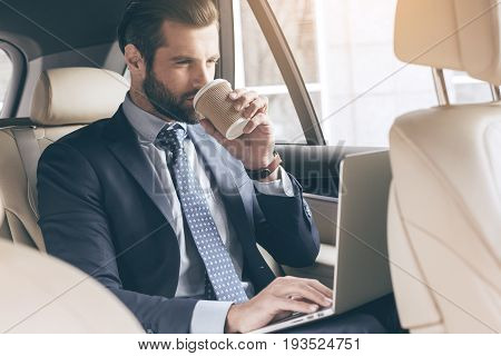 Young business person test drive new vehicle drinking coffee