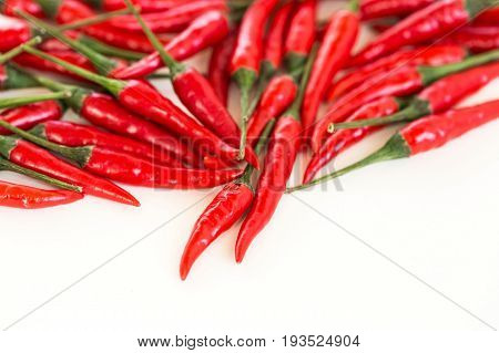 red hot chili peppers, popular spices concept - beautiful handful of red hot pepper in bulk, fresh ripe pods with green peduncle scattered on white background, flat lay, free space for the text.