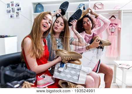 Positive teen girlfriends having fun time together while doing shopping sitting choosing new shoes fooling around and making faces in clothing shop.