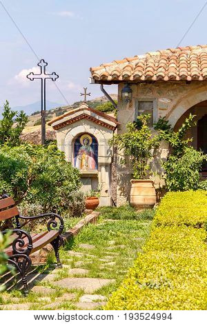 Monastery park with view at chairs, christian icon, flowers and sky. Greece, Corfu