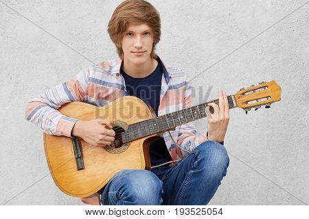 Handsome Young Guy With Stylish Haircut Wearing Shirt And Jeans Playing Guitar, Singing Songs. Cool