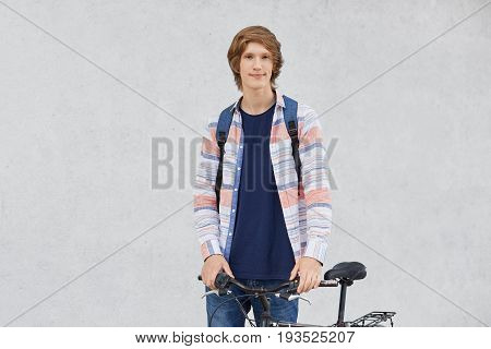 Young Cyclist With Trendy Hairstyle Wearing Shirt And Jeans Holding Rucksack Standing Near His Bicyc