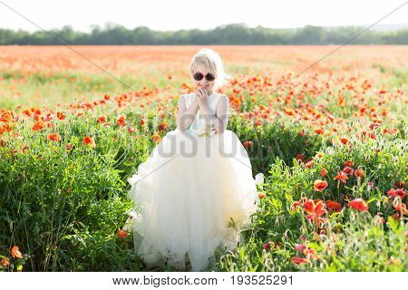 beautiful little girl model in a field of poppies, childhood, happiness, fashion, children, nature and summer flowers concept - cute baby girl in white fashionable dress stand in a field of poppy