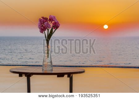 Vase of flowers on table by the swimming pool overlooking sea at sunset in Pomos village Paphos area Cyprus