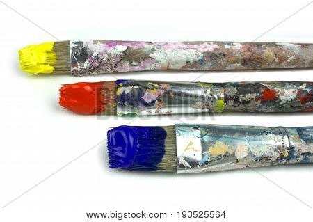 Paintbrushes and primary colors on white background