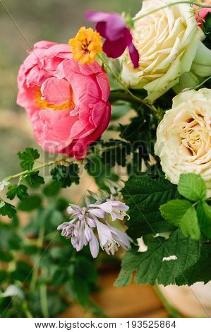 wedding, floral design, arts and crafts, decoration, summer concept - close-up of blooming bright pink peony, creamy english roses and raspberry leaves in beautiful bunch