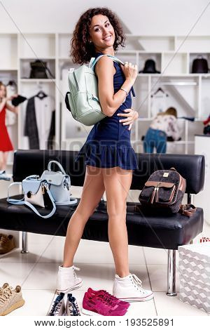Beautiful female shopper standing looking back at camera in new short dress holding backpack wearing sneakers surrounded by variety of shoes and bags in fashion showroom.