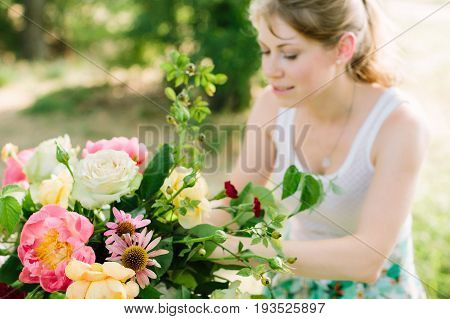 wedding, floral desighn, summer, beauty, nature concept - beautiful fair-haired woman with ponytail making bright multicolored bouquet with roses, pink peonies and red carnation