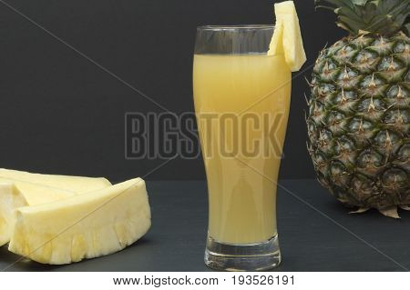 A glass with pineapple juice, a whole pineapple and pineapple chunks