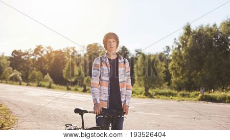 Active Summer Holidays. Portrait Of Young Biker Dessed In Casual Shirt Looking Seriously Into Camera