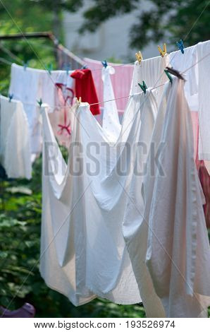 Linen out to dry on the rope.Washing hanging exposed to sunlight.Laundry hanging in a garden