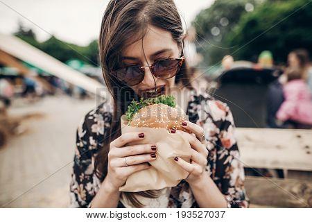 Stylish Hipster Woman Holding Juicy Burger And Eating. Boho Girl With Hamburger  Smiling At Street F