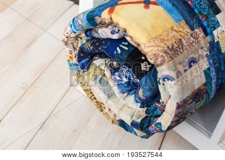 sewing, patchwork and fashion concept - macro of bright blue beautiful multi-colored quilted blanket rolled up in the tube, warehouse of finished needlework products, top view