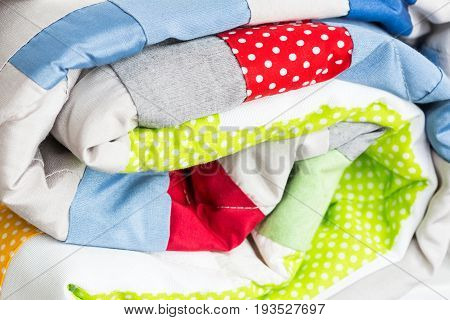 sewing, patchwork and fashion concept - close-up on bright beautiful multi-colored quilt, folded coverlet, finished stitched textile products, side view
