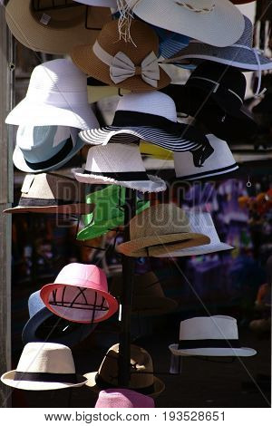 A hat stand with summer hats for women and for men.