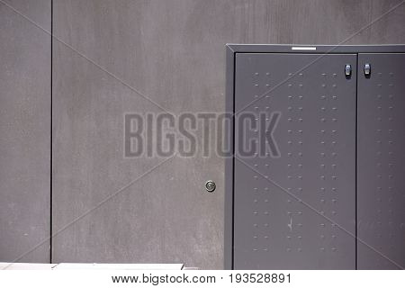 The photograph of a gray electric distribution box against a smooth dark gray wall.