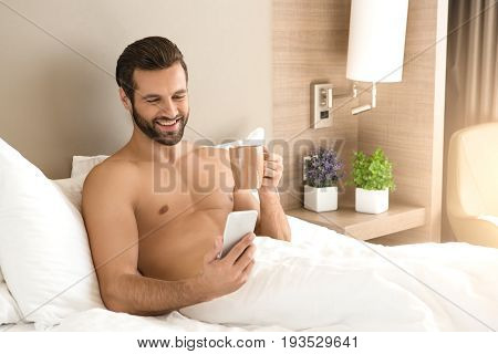Young male traveler tourist hotel accomodation using digital device