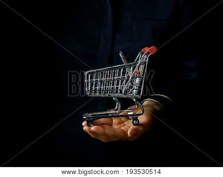 Black Mania. female hand isolated on black background showing mall shopping cart