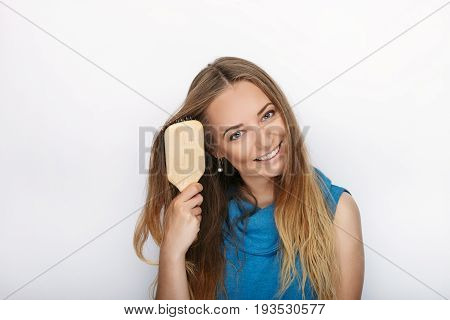 Headshot Of Young Adorable Blonde Woman With Cute Smile With Comb In Hand Brush Her Hair On White Ba