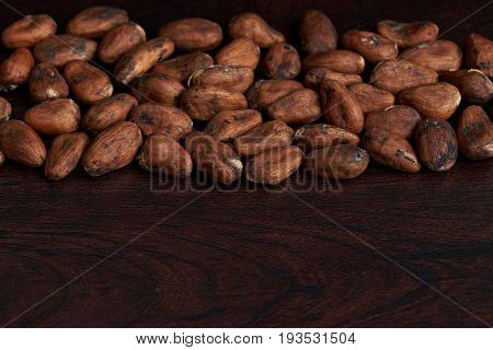 Dry cocoa seeds background. Brown cacao beans on dark wood background