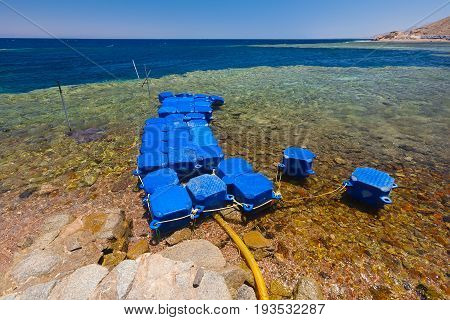 Egypt the Red Sea. Dahab the Blue Hole. The edge of the surf algae and corals. Landscape. The colors are blue yellow green. On the shore the pontoon is made of plastic