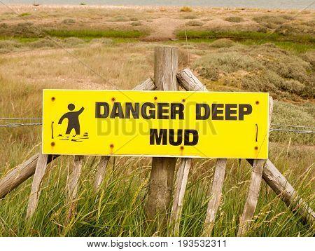 Stock Photo - A Danger Deep Mud Yellow Rectangle Sign Outside Sea Coast