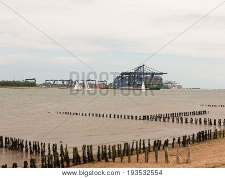 Stock Photo - Blue Sea Structure Cranes At Cargo Dock Loading In Distance Felixstowe Essex Beach In