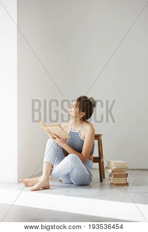 Young beautiful tender girl smiling looking at window holding book sitting on floor over white wall early in morning. Copy space.