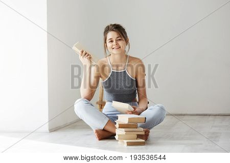 Young beautiful tender girl smiling looking at camera holding book sitting on floor over white wall early in morning. Copy space.