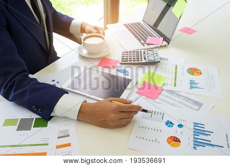 Concept of a business man analyzes data online with the internet and eating coffee,Businessmen are analyzing graphs and on the desk with a laptop tablet calculator and eat coffee.