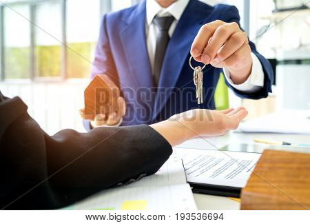 Salespeople deliver home keys to customers,Customers receive home keys from home sales sales,Home sales concept image.