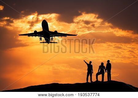 Landscape with silhouettes of a standing man pointing finger on passenger airplane flying in the colorful sky and his friends on the mountain peak at sunset. Taking off airplane. Commercial aircraft