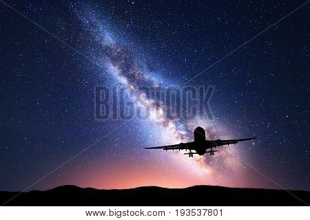 Milky Way and silhouette of a airplane. Landscape with passenger airplane is flying in the starry sky at night. Space background. Commercial airliner on the background of colorful Milky Way. Aircraft