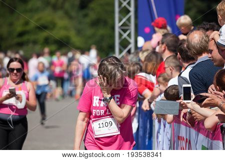 SOUTHAMPTON UK - July 2 2017: Race for Life women run and walk to raise money for Cancer Research charity in Southampton UK. Woman crying after completing race emotional day remembering lost ones.