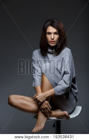 beautiful girl in oversize grey sweater sitting on bar stool. studio portrait on dark background. copy  space.