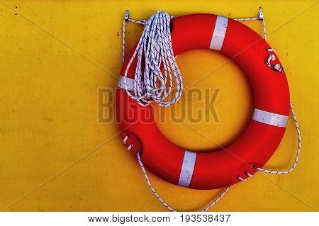 Life saver buoy hanging in a yellow wall of seaship. Greece, Corfu