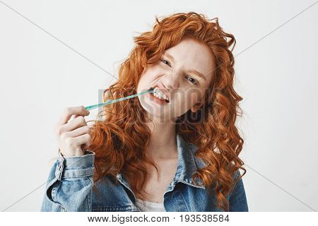 Cool brutal redhead girl in jean jacket chewing gum looking at camera over white background.