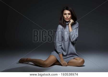 beautiful girl in oversize grey sweater sitting on floor. studio portrait on dark background. copy  space.