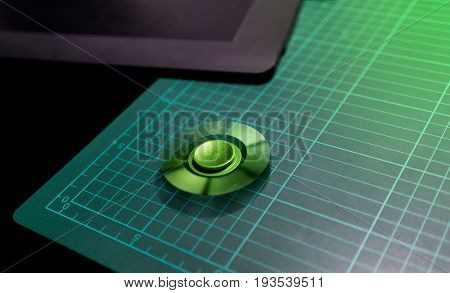 Green aluminum fidget spinner stress relieving toy spinning on top of cutting mat