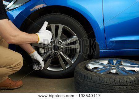 Wheel change service. Man change damage car wheel