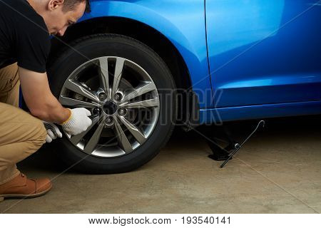 Changing modern car wheel. Man fixing car wheel