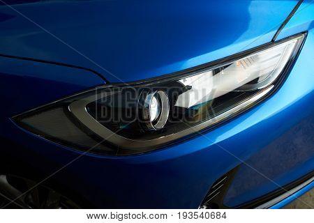 Clean modern car headlight close-up. Polished car frontlight