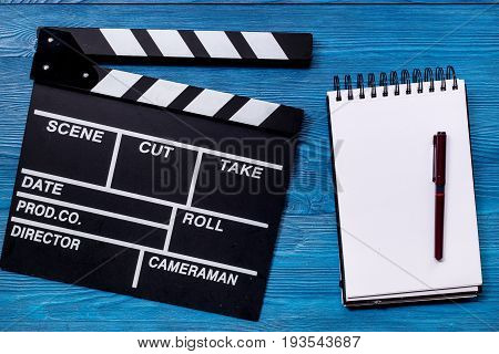 Work table of producer. Movie clapperboard and notebook on blue wooden table background top view.