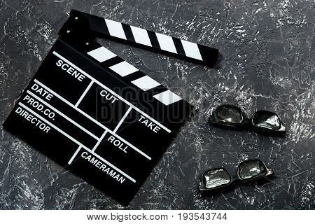 Attributes of film director. Movie clapperboard and sunglasses on grey stone table background top view.
