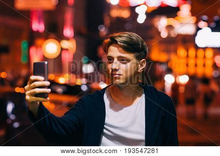 Young man take selfie on smartphone while walking in night city streets. Smiling guy on blurred lights background