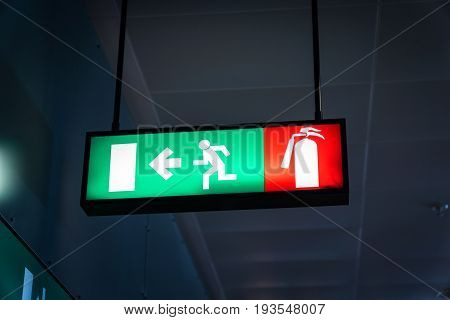 Emergency fire exit sign glowing green in the blacked out background at airport