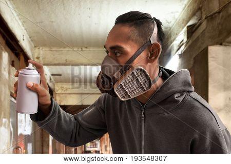 Graffiti artist wearing respirator mask on the street
