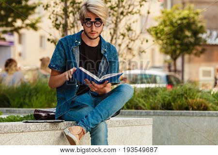 Hipster Guy Holding Notebook Sitting On Ledge