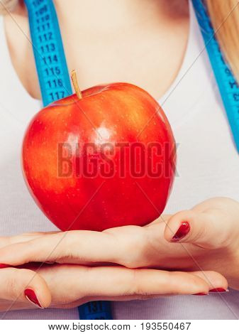 Woman With Measuring Tape Around Neck Holding Apple