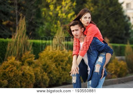 Guy rolls his girlfriend Piggyback. Enamored teenagers. Fun and romance of the first date.